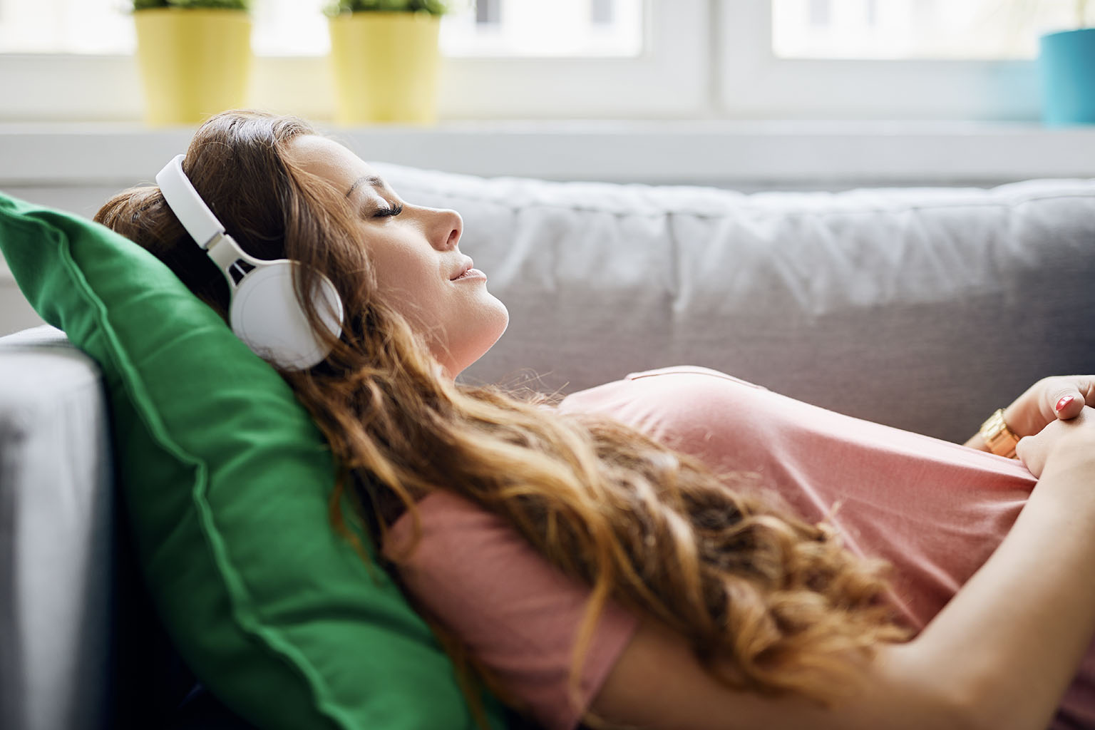 Jak radzić sobie ze stresem i napięciem? Kobieta ze słuchawkami na uszach leży na kanapie i słucha muzyki.