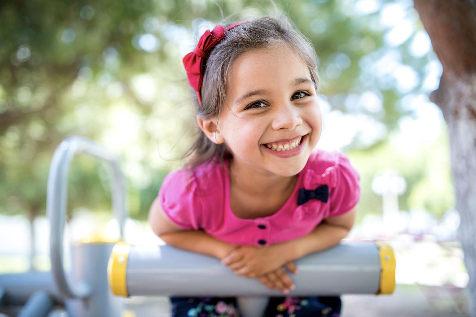 Jak rozwijać kreatywność u dzieci? Mała dziewczynka na placu zabaw uśmiecha się do aparatu.