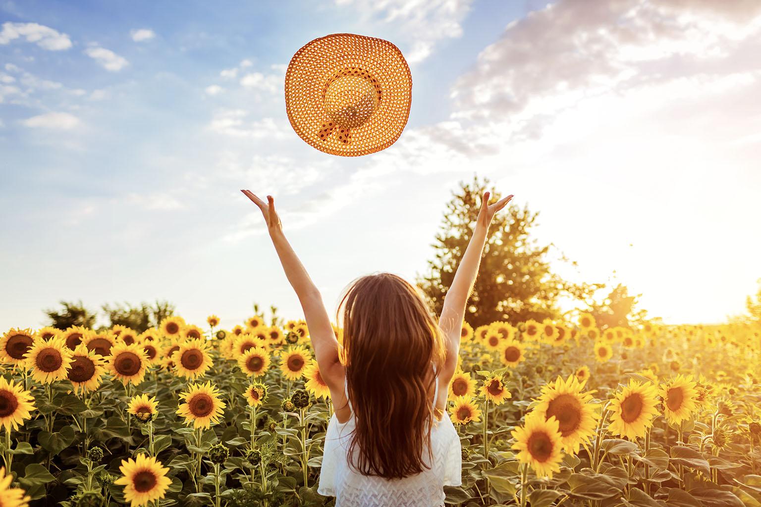 Jak wzmocnić odporność u dorosłych? Młoda kobieta stoi w polu słoneczników i podrzuca do góry słomkowy kapelusz.