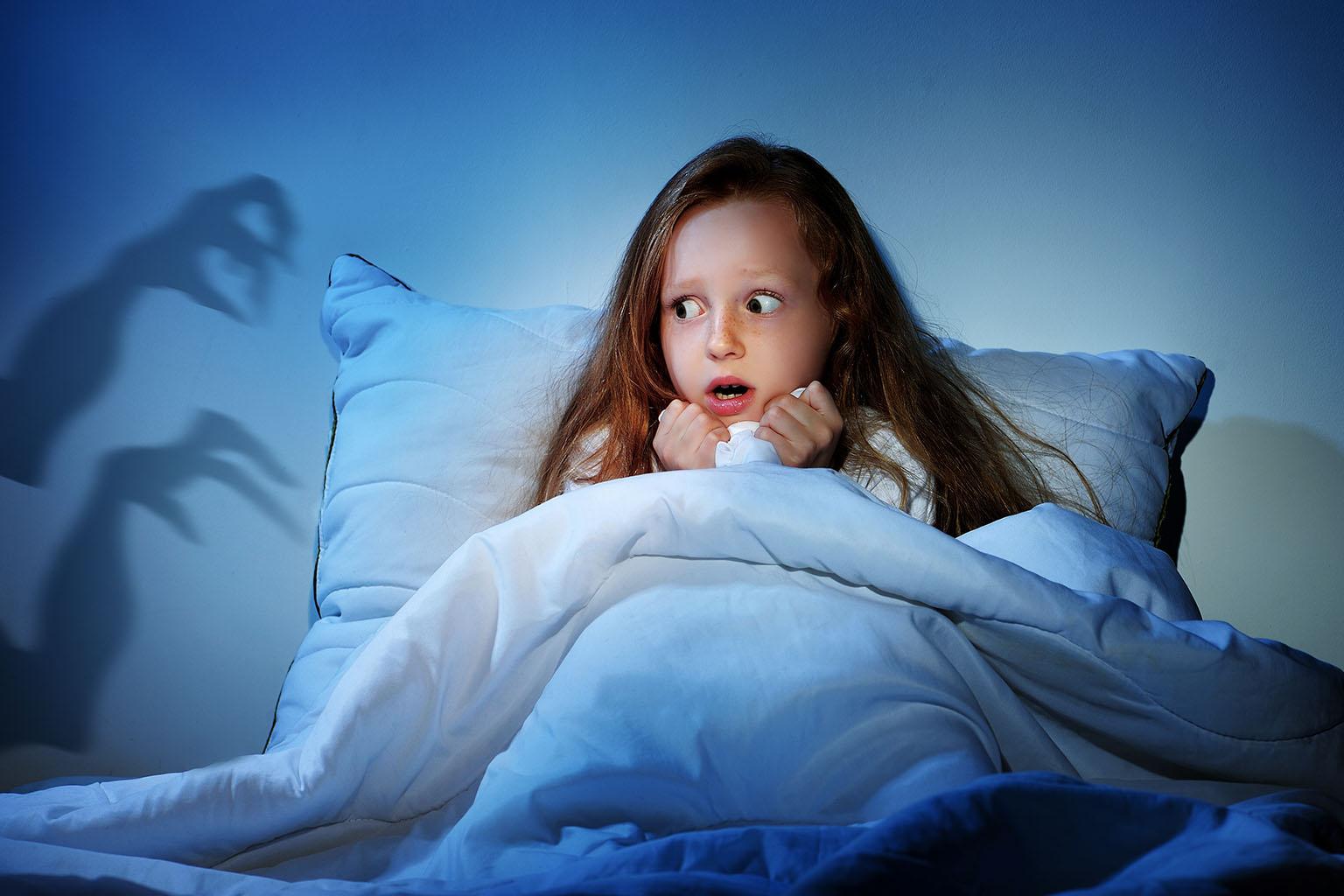 Co zrobić, gdy dziecko boi się ciemności? Dziewczynka skrywa się w łóżku pod kołdrą - boi się, że z ciemności wyjdą potwory - na ścianie widać cienie szponów.