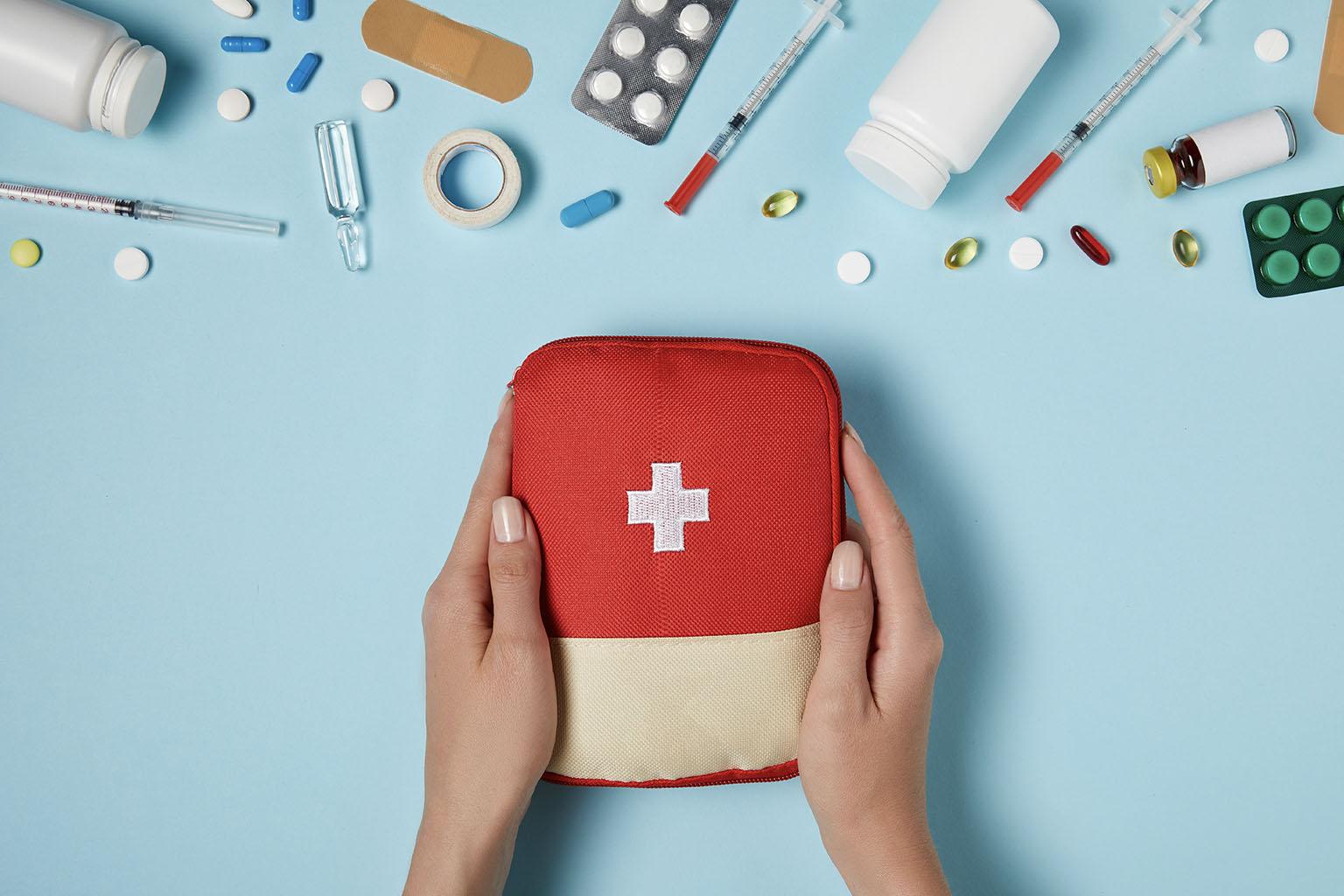 Co powinna zawierać domowa apteczka? Kobiece dłonie trzymające czerwoną apteczkę.