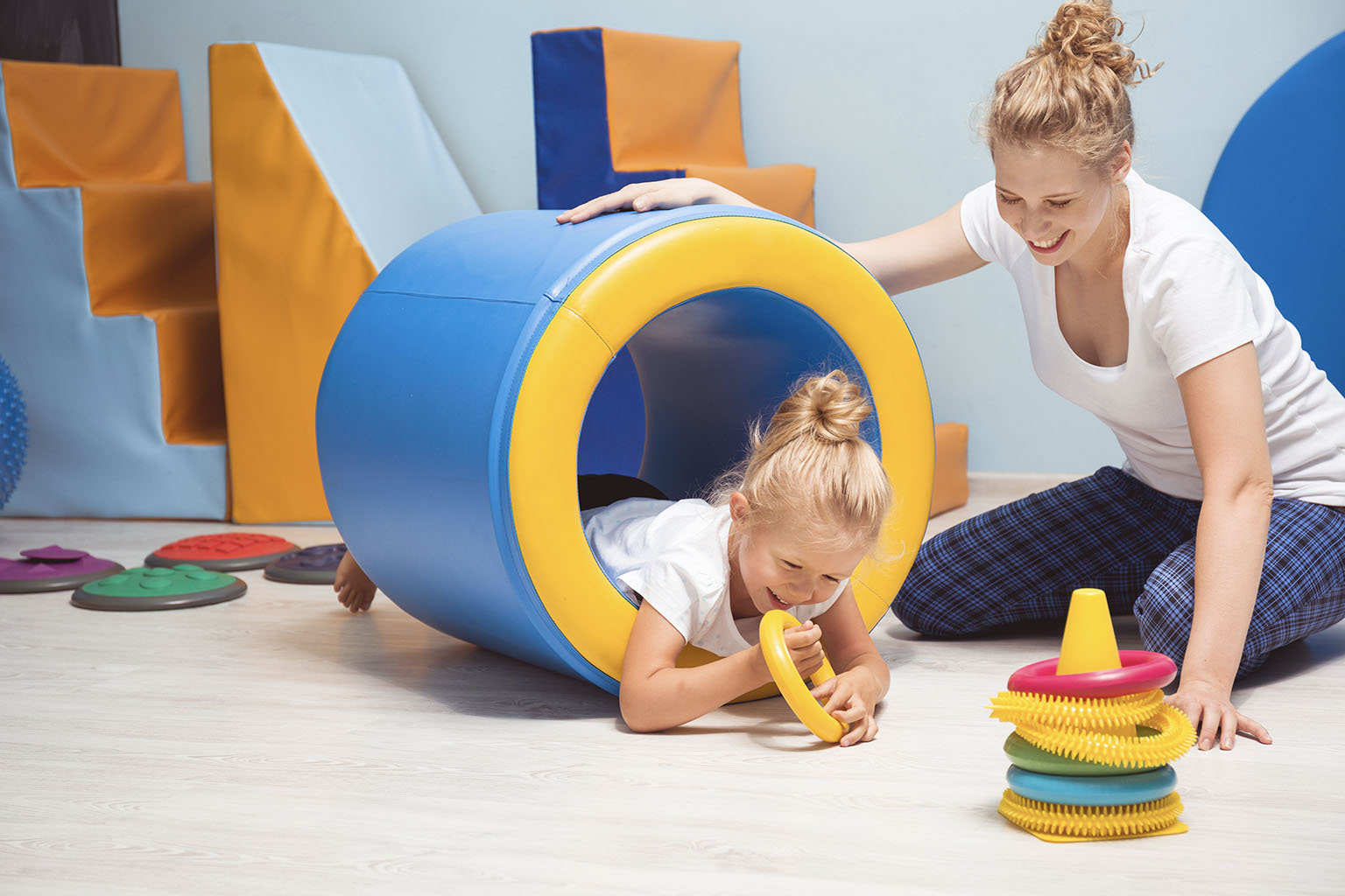 Czym jest integracja sensoryczna i jak przebiegają zajęcia z SI? Dziewczynka przechodzi przez tunel na ścieżce sensorycznej na zajęciach z integracji sensorycznej.