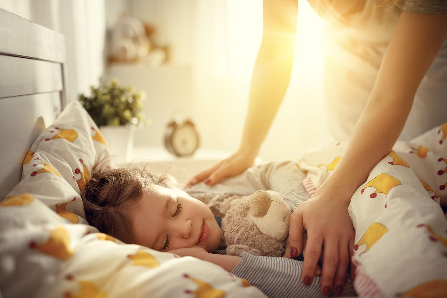 Jak nauczyć dziecko spania we własnym łóżku? Mama przykrywa kołdrą córeczkę śpiącą we własnym łóżeczku w pokoju dziecięcym.