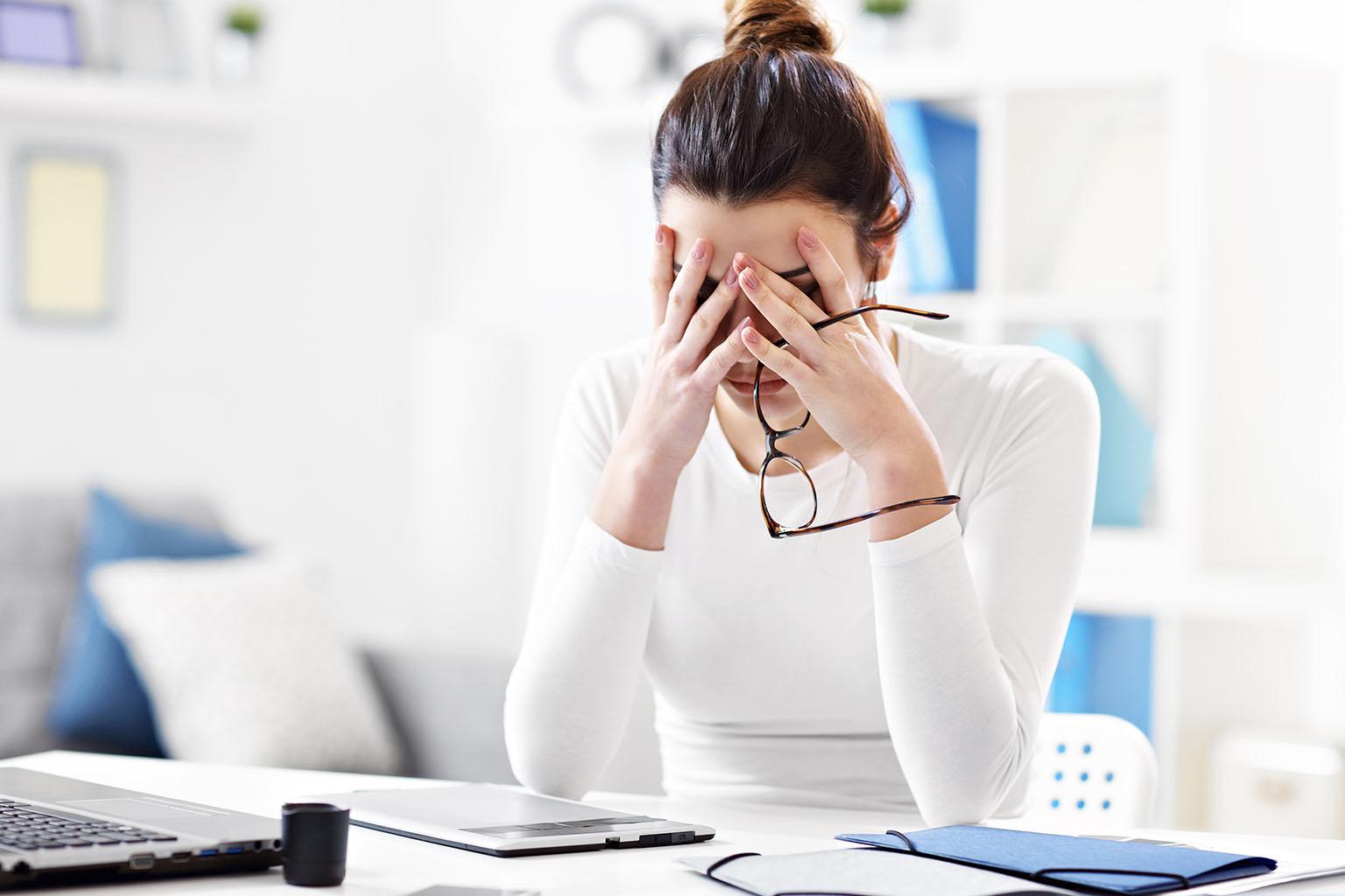 Jak stres wpływa na organizm? Jak radzić sobie ze stresem? Kobieta skrywa głowę w dłoniach z powodu stresu w pracy.