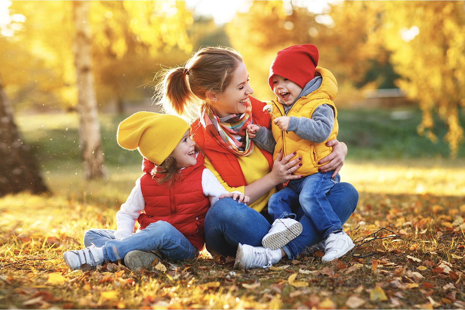 Jak wzmocnić odporność u dzieci? Kolorowa ubrana mama z dziećmi bawi się w jesiennych liściach.