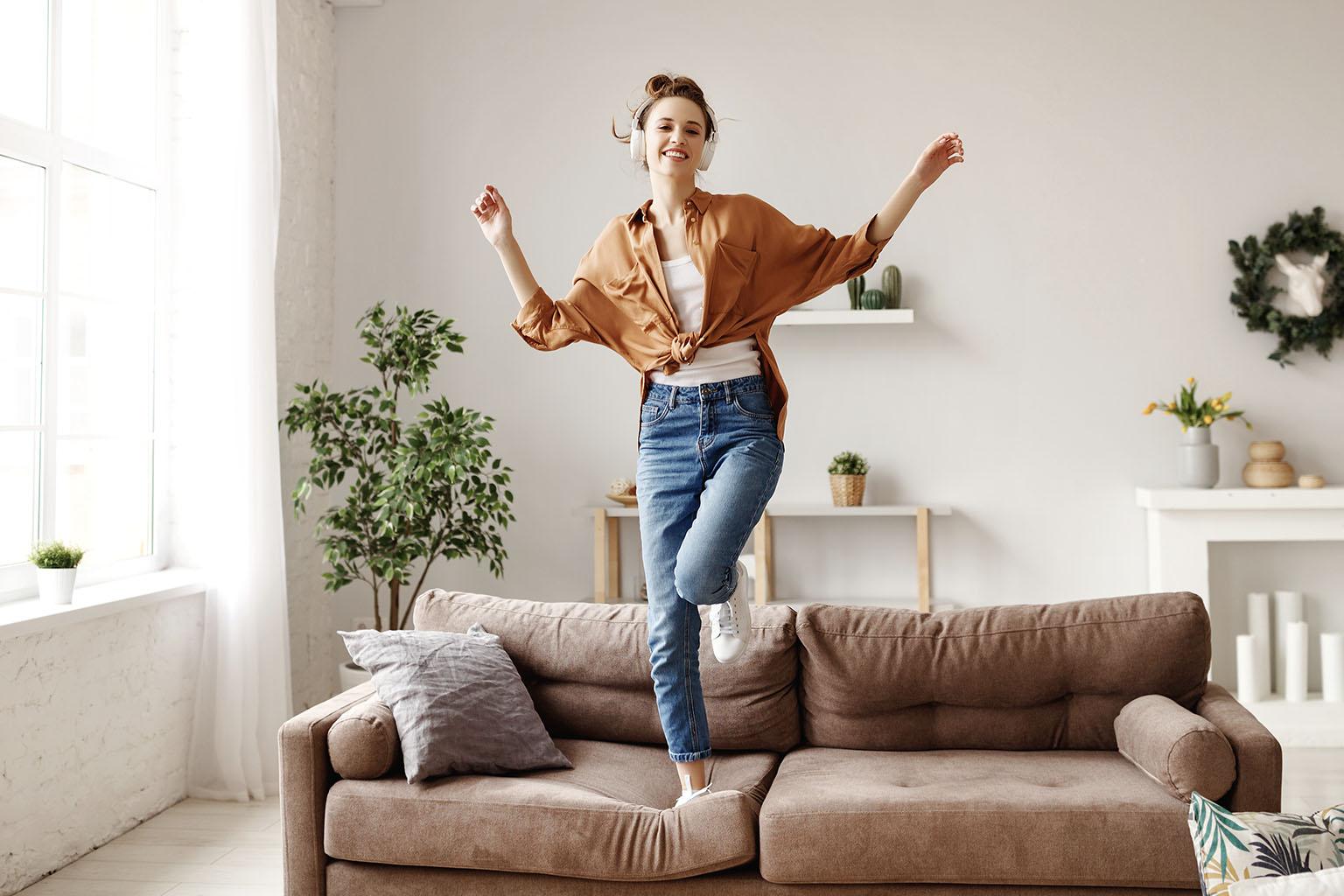 Sposoby na poprawę humoru, czyli jak odzyskać dobry humor. Kobieta ze słuchawkami na uszach skacze po kanapie.
