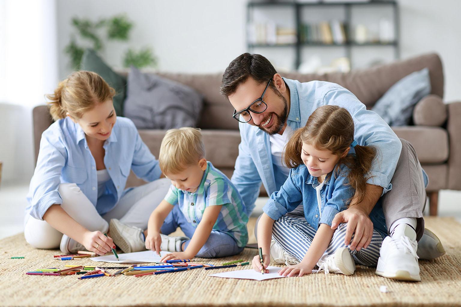 Zabawy dla dzieci - w co się bawić z dzieckiem w domu? Rodzice bawią się z dziećmi na podłodze w salonie.