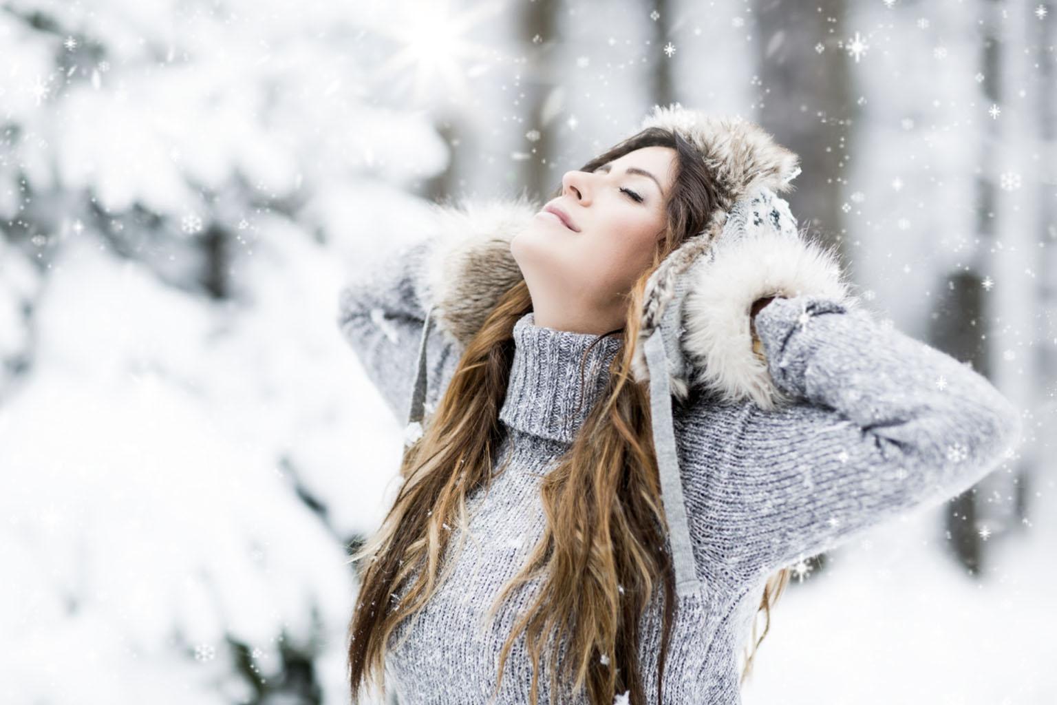 Hartowanie organizmu – jak robić to z głową? Ciepło ubrana dziewczyna spaceruje po śniegu.