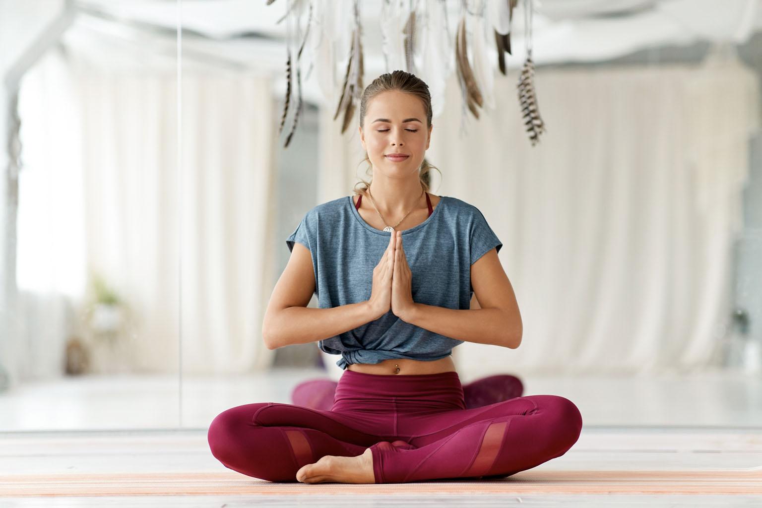 Techniki relaksacyjne – jak rozładować stres? Kobieta medytuje w sali gimnastycznej.